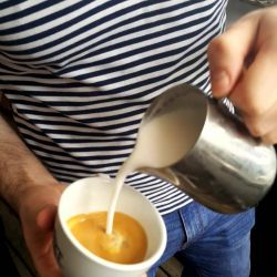 Barista in striped Tshirt playing with some Costa
